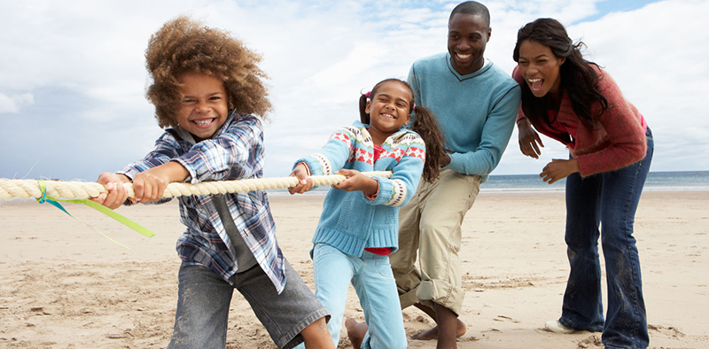 African-American family playing tug-of-rope on a beach. A young boy, girl, mother, father.
